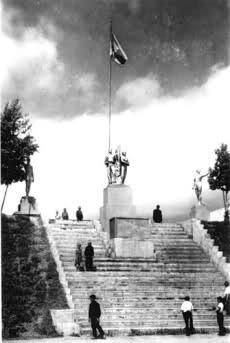 Лестница на стадионе в парке. Вверху скульптура  «Советские спортсмены – за мир», созданная С. Горпенко и А. Косяковым