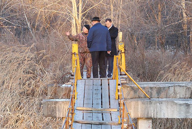 Вместо навесного мостика через реку нужны капитальный мост и дорога