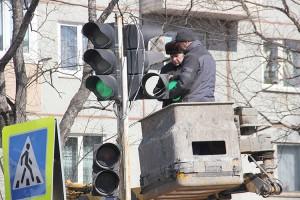 Работники строительной компании «ПШСУ» меняют линзу на светофоре возле школы №6